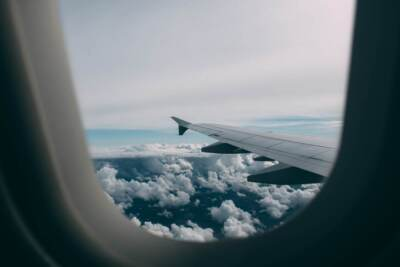 View of an airplane's wing and top of clouds from window.   Rubber components