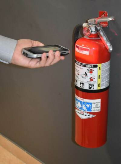 Someone checking the status of a fire extinguisher with fire extinguisher inspection software