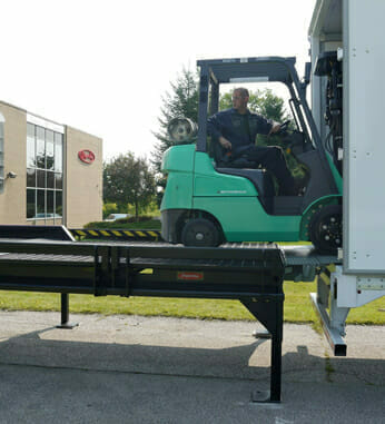 Green forklift entering semi-truck trailer with portable yard ramp