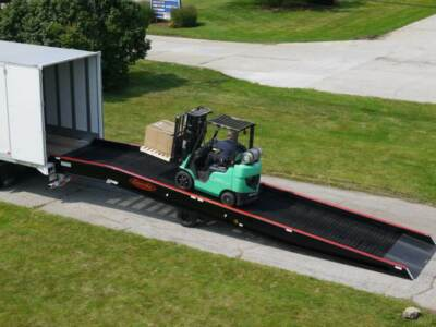 Green forklift carrying pallet up semi truck ramp