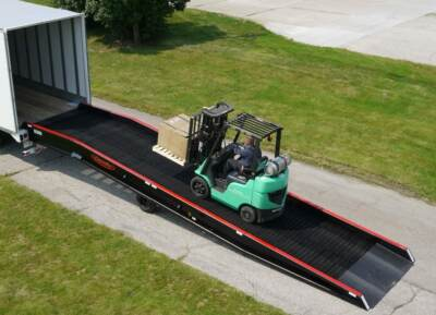 Green forklift carrying pallet up yard ramp to semi truck bed