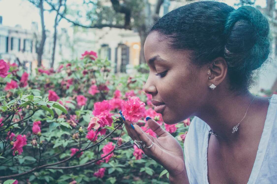 A woman smelling some flowers   Greenhouse digital marketing