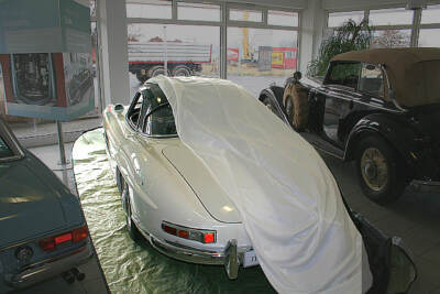 White car with rust cover draped over it