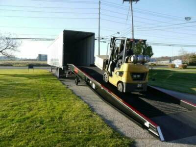 Forklift traveling up a semi truck ramp
