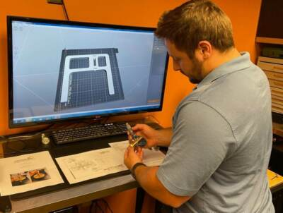 An engineer looking at a blueprint of a G Force part