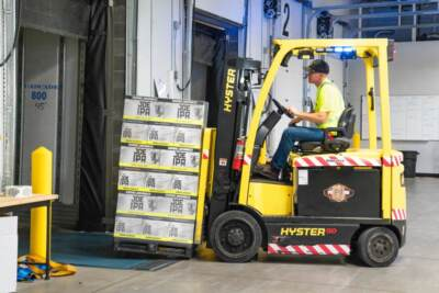 Yellow forklift carrying large pallet of materials | Yard ramp forklift safety