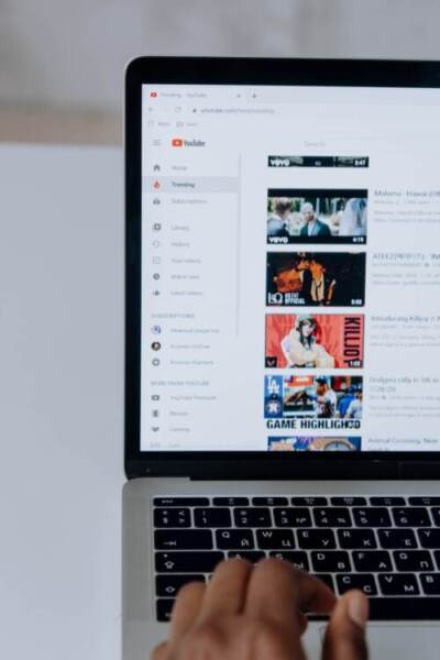 Half of laptop screen displaying list of YouTube videos | YouTube video descriptions